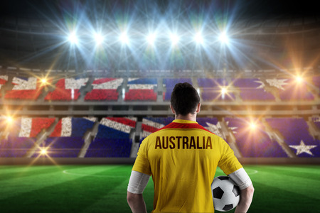 Australia football player holding ball against stadium full of australia football fans photo