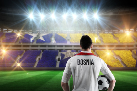 Bosnia football player holding ball against stadium full of bosnia football fans photo