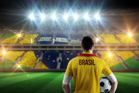 Brasil football player holding ball against stadium full of brasil football fans photo
