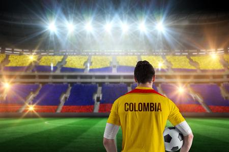 コロンビアのスタジアム絶頂に対してフットボールのファンのボールを保持してコロンビアのフットボール選手 写真素材