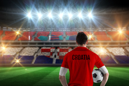 Croatia football player holding ball against stadium full of croatia football fans photo