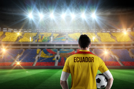 Ecuador football player holding ball against stadium full of ecuador football fans photo