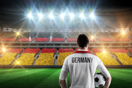 Germany football player holding ball against stadium full of germany football fans photo