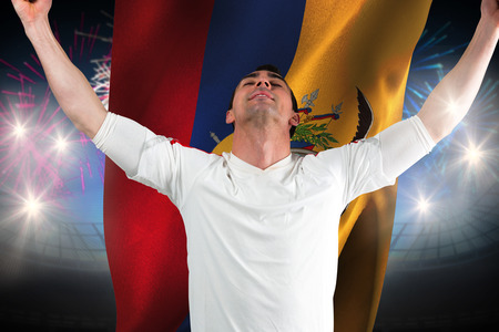 Excited football fan cheering against fireworks exploding over football stadium and ecuador flag photo