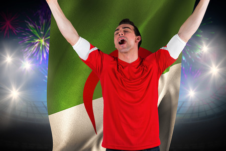 Excited football fan cheering against fireworks exploding over football stadium and algeria flag photo