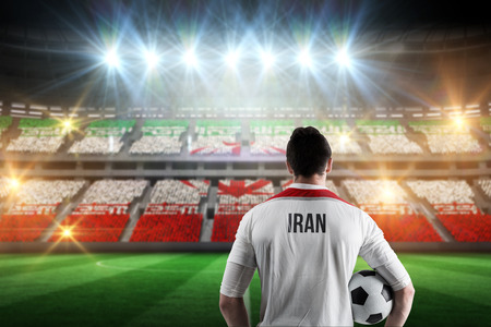 Iran football player holding ball against stadium full of iran football fans photo