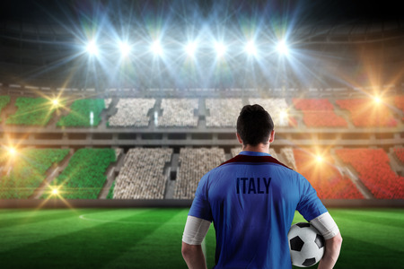 Italy football player holding ball against stadium full of italy football fans photo