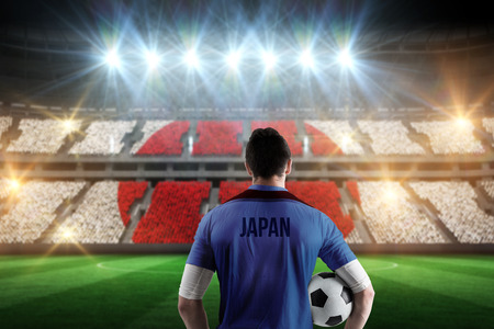 Japan football player holding ball against stadium full of japan football fans photo