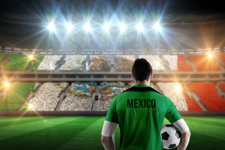 football world cup: Mexico football player holding ball against stadium full of mexico football fans Stock Photo