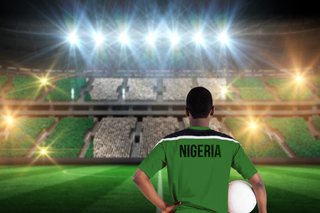 Nigeria football player holding ball against stadium full of nigeria football fans photo