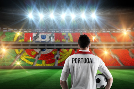 Portugal football player holding ball against stadium full of portugal football fans photo