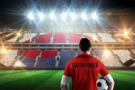 South korea football player holding ball against stadium full of korea football fans photo