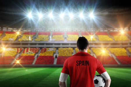 Spain football player holding ball against stadium full of spain football fans photo