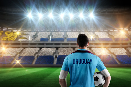 Uruguay football player holding ball against stadium full of uruguay football fans