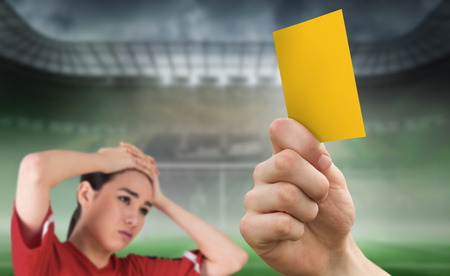 Composite image of hand holding up yellow card to fan against football pitch in large stadium photo