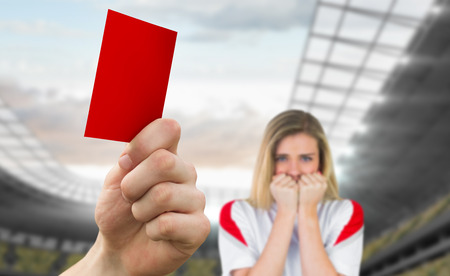 Composite image of hand holding up red card to fan against football stadium photo