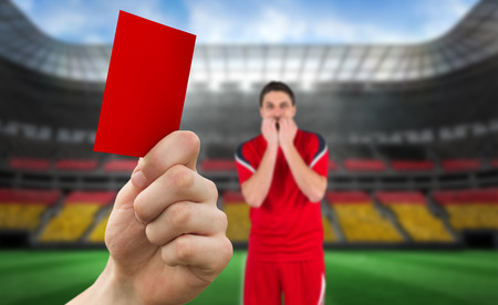 Composite image of hand holding up red card to player against stadium full of germany football fans photo