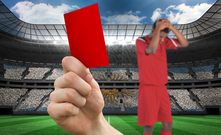 Composite image of hand holding up red card to player against stadium full of argentina football fans photo