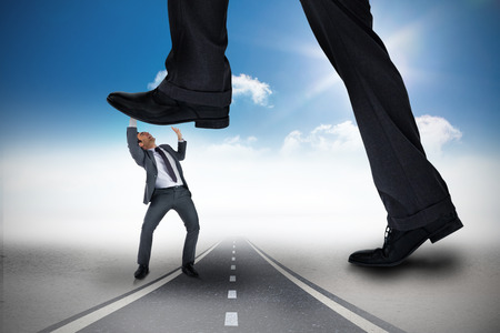 Composite image of businessman stepping on tiny businessman against open road photo
