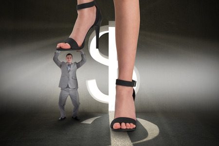 Composite image of female feet in black sandals stepping on tiny businessman against grey room with dollar door photo