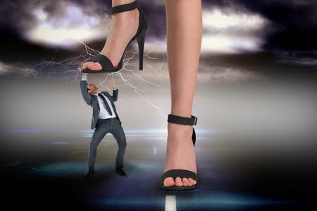 dominacion: Imagen compuesta de pies femeninos en sandalias negras pisando empresario contra el cielo tempestuoso sobre la carretera con el relámpago Foto de archivo