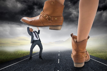 Composite image of cowboy boots stepping on businessman against stormy landscape background with street photo