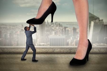 Composite image of businesswoman stepping on tiny businessman against balcony overlooking city photo