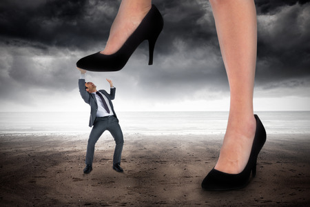 dominating: Composite image of businesswoman stepping on tiny businessman against stormy weather by the sea