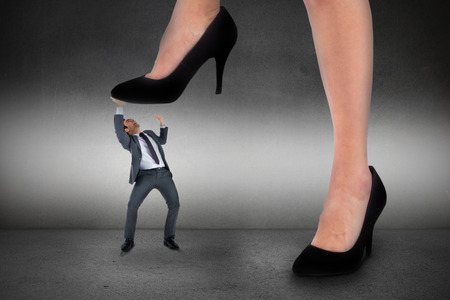 Composite image of businesswoman stepping on tiny businessman on grey background photo