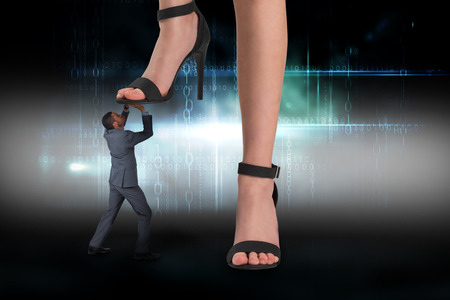 dominance: Composite image of female feet in black sandals stepping on businessman against black technology design with glow Stock Photo