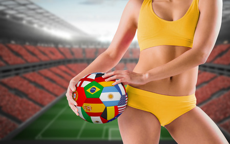 Fit girl in yellow bikini holding flag football against vast football stadium with fans in red photo