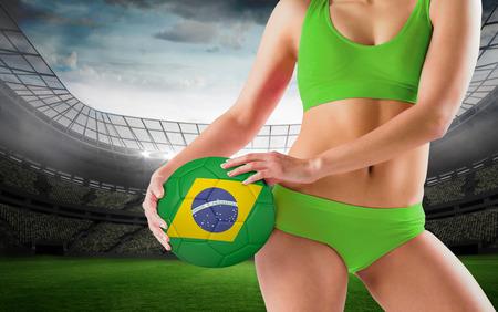 Fit girl in green bikini holding brasil ball against large football stadium with lights photo