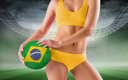 Fit girl in yellow bikini holding brazil football against misty football stadium under spotlights photo