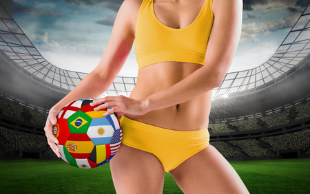 Fit girl in yellow bikini holding flag football against large football stadium with lights photo