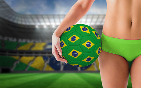 Fit girl in green bikini holding brazil football against large football stadium with brasilian fans photo
