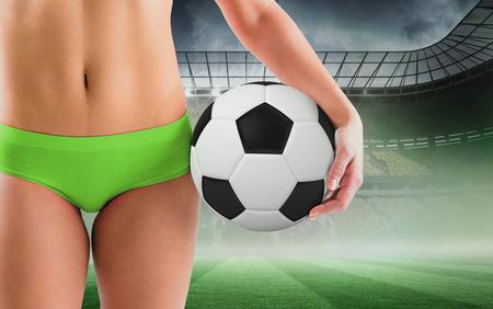 Fit girl in green bikini holding football against misty football stadium under spotlights photo