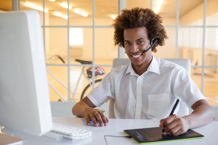 Casual young businessman using digitizer and headset at desk in his office photo
