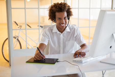 digitizer: Casual young businessman using digitizer and headset at desk in his office