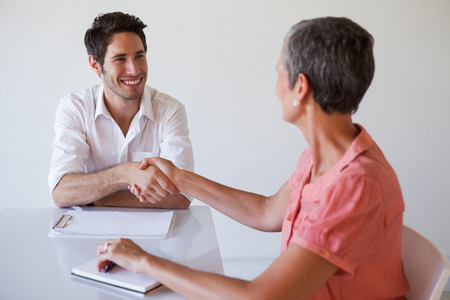 Casual business people shaking hands at desk and smiling in the office photo