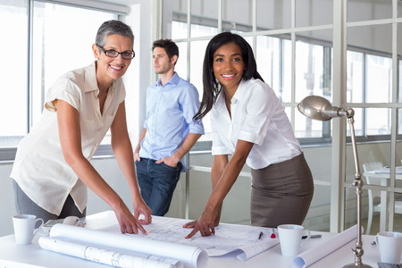 Smiling architects analyzing plans together in the office  photo