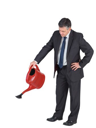 Mature businessman watering with red can on white background Stock Photo