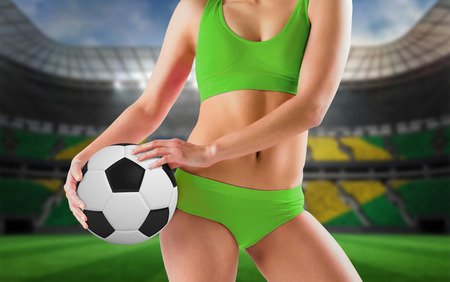 Fit girl in green bikini holding football against large football stadium with brasilian fans photo