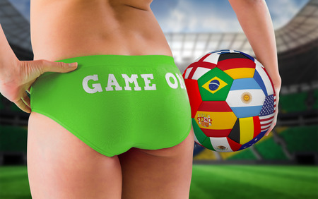 Fit girl in green bikini holding flag football  against large football stadium with brasilian fans photo