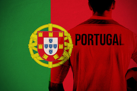 Portugal football player holding ball against portugal national flag photo