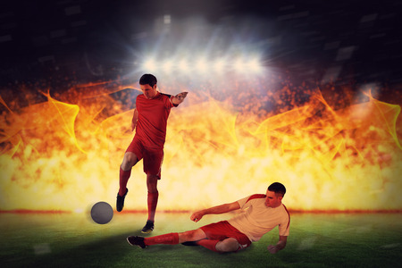 Football players tackling for the ball against football pitch under spotlights Stock Photo - 29047607