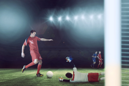 Football players tackling for the ball against football pitch under spotlights Stock Photo - 29047609