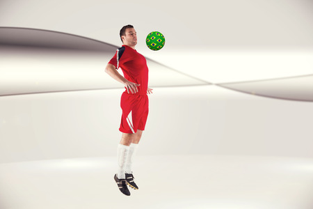 Football player in red jumping against futuristic bright grey background photo