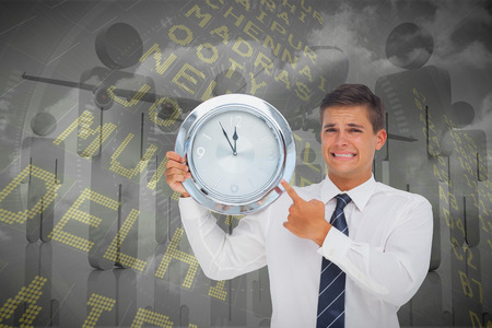 Anxious businessman holding and showing a clock against airport departures board for india photo