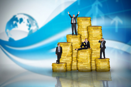 Composite image of business people on pile of coins against global business graphic in blue photo