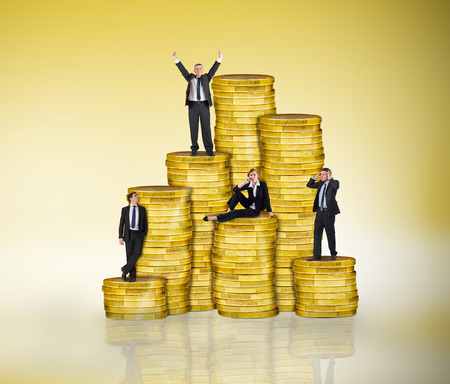 Composite image of business people on pile of coins against yellow vignette photo
